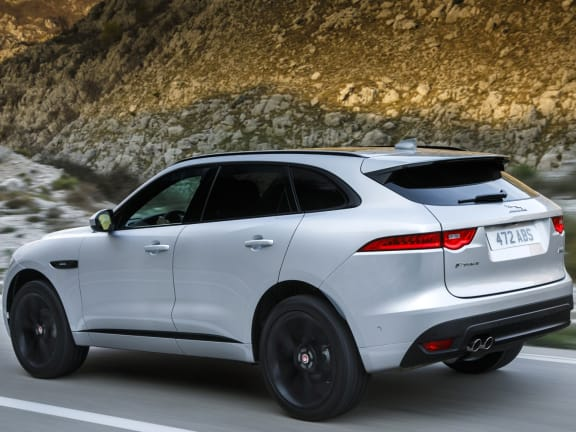 Side view of Jaguar F-Pace driving on a road