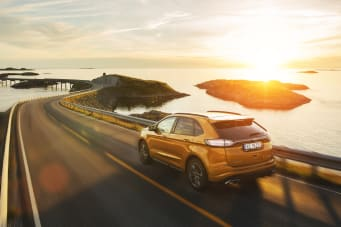 Orange Ford Edge Driving In Sunset