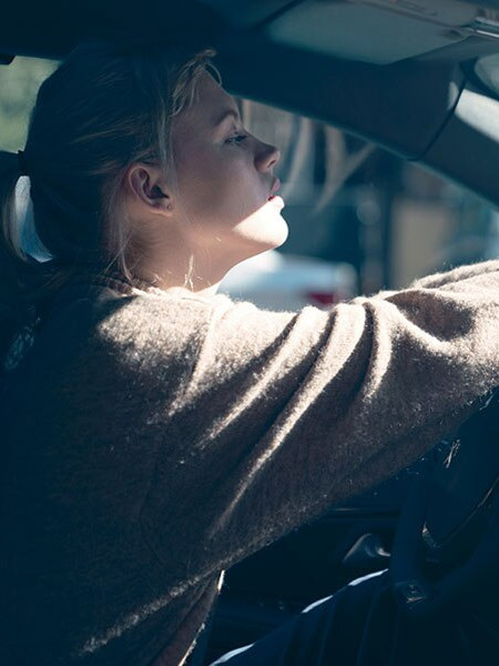 Blonde woman driving a Peugeot 208