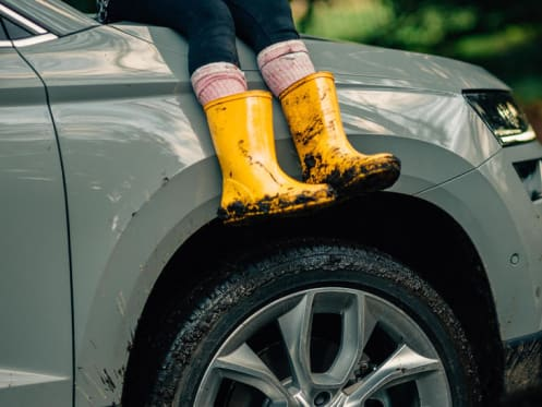 Child with muddy yellow wellies sat on bonnet of skoda suv