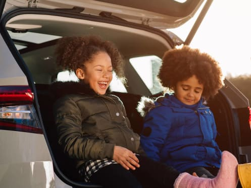 Two children, a girl and a boy, sat in the boot of a skoda suv laughing