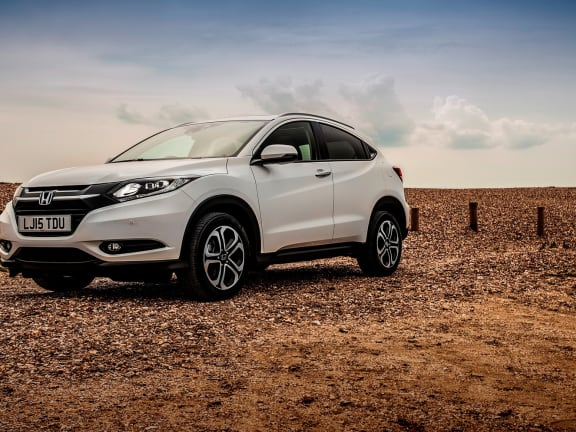 Front view of a white Honda HR-V parked on beach pebbles