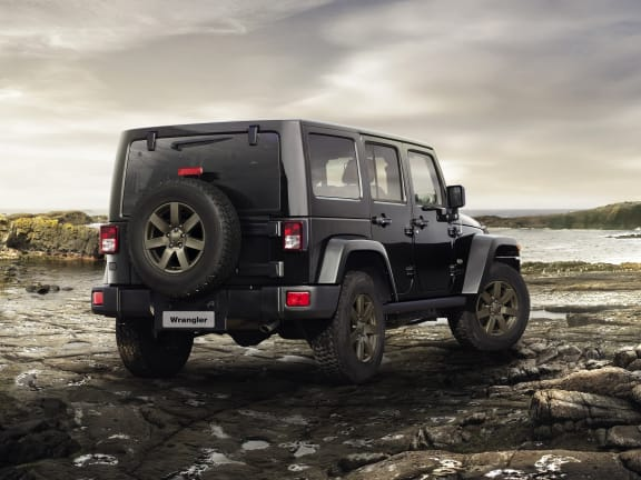 rear view of a Black Jeep Wrangler parked on rocks