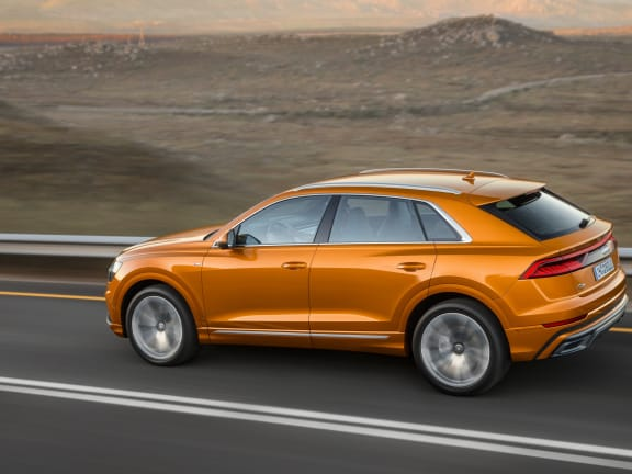 Side view of an orange Audi Q8 driving on a road